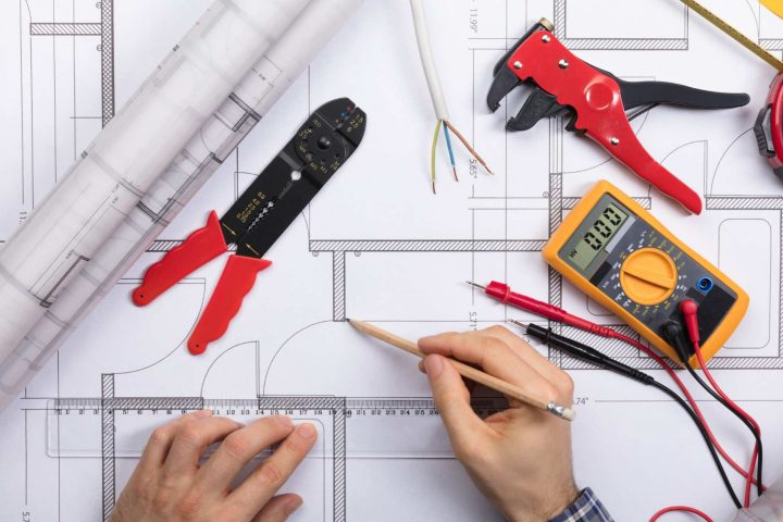 Elevated View Of An Architect Drawing Plan On Blueprint With Electrical Components